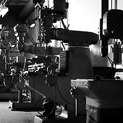 Black and white shot of row of drill presses at machine shop in San Diego