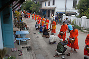 "Luang Prabang, Laos. Every morning at dawn, barefoot Buddhist monks and novices in orange robes walk down the streets collecting food alms from devout, kneeling Buddhists. They then return to their temples (also known as ""wats"") and eat together. This procession is called Tak Bat, or Making Merit. ."