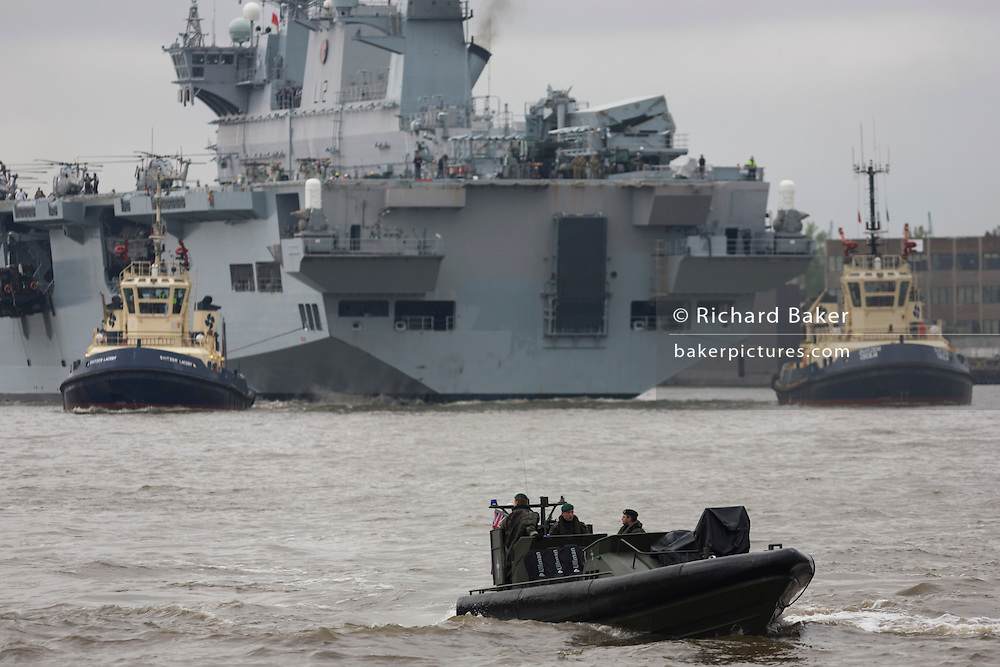Royal Marines in a Rigid Hull Inflatable Boat (RIB), accompanying HMS Ocean (L12) upstream on the River Thames towards Greenwich ahead of a major security exercise in preparation for the 2012 Olympic Games. Ocean is an amphibious assault ship (or landing platform helicopter), the sole member of her class and the Royal Navy's largest ship. She then berthed at Greenwich in east London, close to the main Olympic venue where it will act as a launch pad for eight army Lynx helicopters from 661 Squadron and a base for Royal Marine snipers, able to shoot at the engines of fast-moving targets. It is the final phase of the exercise named Olympic Guardian, which began earlier this week in Weymouth, England and in the airspace over the capital. During the actual Olympics in July, Ocean will be moored in Greenwich to provide logistics support, accommodation to 9 Assault Squadron Royal Marines and a helicopter landing site. HMS (Her Majestys Ship) Ocean was constructed in the mid 90s at a cost of £234 million, the 203.4m (667 ft) long, 21,500 tonnes. .