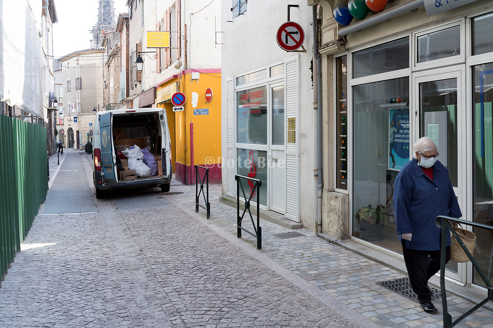 senior woman walking in the street with face mask during the Covid 19 crisis and lockdown France Limoux April 2020