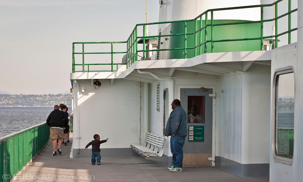 A young boy waves to his dad as he walks toward some older boys as if to tell his dad that he'll be hanging out with the boys. on a Washington State Ferry in Puget Sound, Washington.