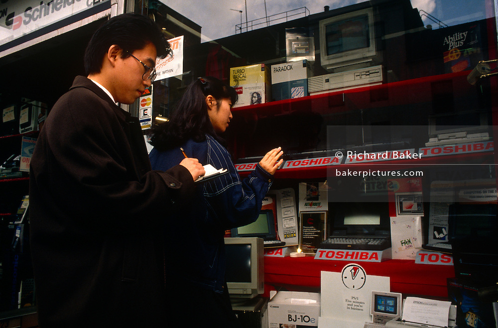 Two people of east Asian-descent look at Toshiba laptops displayed in a computer specialist in Tottenham Court Road - the centre for technology, gadgets and computing in central London. It is 1990 and the smaller, more portable laptop market is just taking off. The man takes notes on paper, writing prices, technical  specifications and offers for these Japanese-made items. Vying for sales with Toshiba in this particular window is Psion, Epson and Canon - all players in the early 1990s.