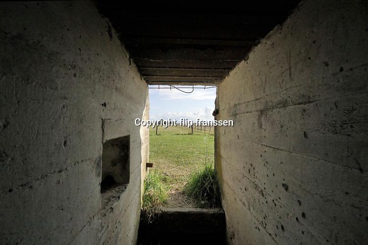 Nederland, Zeeuws Vlaanderen, Groede, 12-9-2019 . Duitse bunker uit de tweede wereldoorlog . Deze was onderdeel van de Atlantik Wall, de kustverdediging van noordwest europa tegen een invasie . Bij Groede ligt het zgn bunkerdorp, een aantal bunkers die militairem huisvesten die twee kanonnen bedienden en in opleiding waren. De betonnen kazematten werden door hen beschilderd met ramen en gordijnen als camouflage zodat het gewone huizen leken. Nu gebruken kinderen ze om op te klimmen en is het nepdorpje een museum, oorlogsmuseum. Foto:Flip Franssen