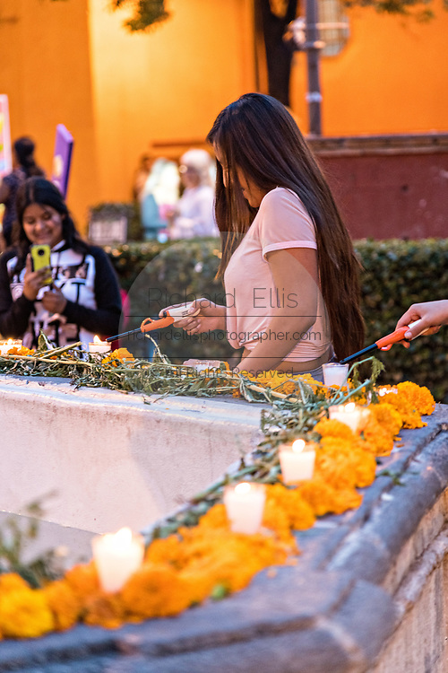A Mexican girl lights candles on a Dead of the Dead altar known as an ofrenda honoring deceased relatives during the Dia de Muertos festival in San Miguel de Allende, Mexico. The multi-day festival is to remember friends and family members who have died using calaveras, aztec marigolds, alfeniques, papel picado and the favorite foods and beverages of the departed.