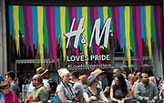 Pride in London, formally known as Pride London, is an annual LGBT pride festival and parade held each summer in London, United Kingdom. People wait to watch the parade in front of H&M shop window which is decorated with rainbow coloured stripes.