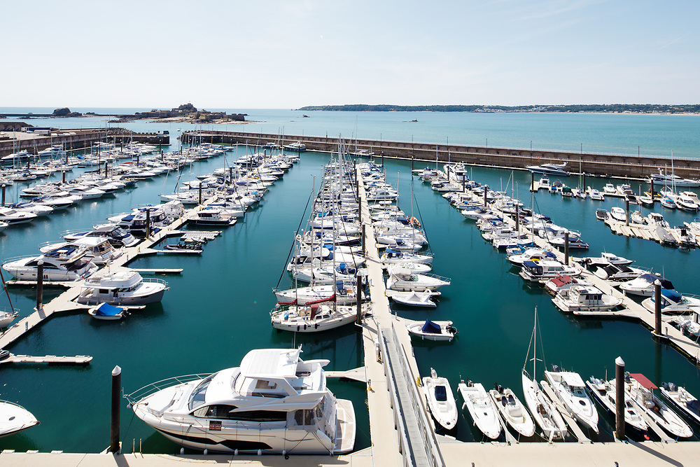Boats and yachts moored up at Jersey harbour with Elizabeth Castle, the historic heritage site and tourist attraction, beyond.