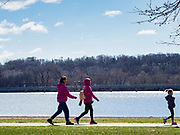 """29 MARCH 2020 - DES MOINES, IOWA: People social distance while they walk around Gray's Lake, a popular park and lake near downtown Des Moines. On Sunday morning, 29 March, Iowa reported 336 confirmed cases of the Novel Coronavirus (SARS-CoV-2) and COVID-19. There have been four deaths attributed to COVID-19 in Iowa. Restaurants, bars, movie theaters, places that draw crowds are closed until 07 April. The Governor has not ordered """"shelter in place""""  but several Mayors, including the Mayor of Des Moines, have asked residents to stay in their homes for all but the essential needs. People are being encouraged to practice """"social distancing"""" and many businesses are requiring or encouraging employees to telecommute.        PHOTO BY JACK KURTZ"""
