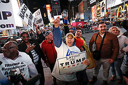 © Licensed to London News Pictures. 09/11/2016. New York City, USA. A man carrying a pro Trump sign reacts to news that Donald Trump looks likely to be elected as the next president of the United States, while gathering in Times Square, New York City, on Wednesday, 9 November. Photo credit: Tolga Akmen/LNP