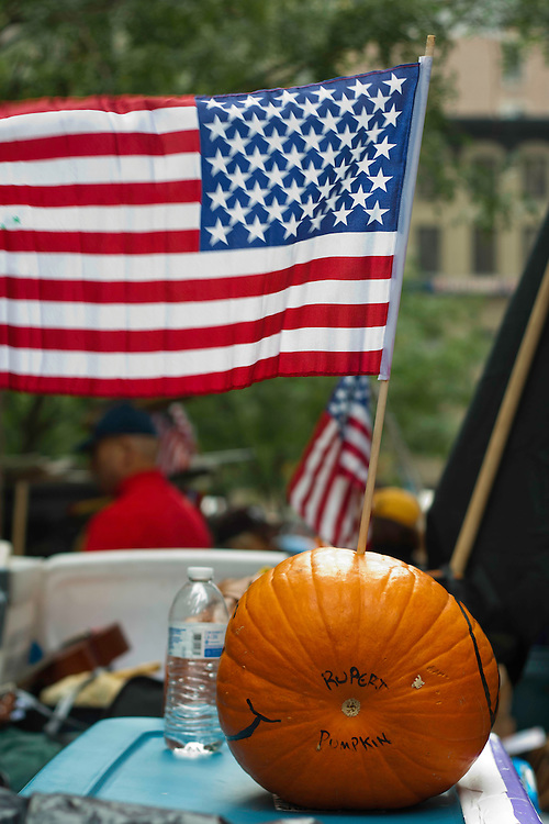 """Pumpkin nicknamed """"Rupert Pumpkin"""" sits on a wall in Zuccotti Park while protesters gather nearby. October 21, 2011"""