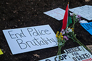 Protest signs and flowers are seen at the Allen Street Gates after a protest in State College, Pennsylvania on March 19, 2021. The 3/20 Coalition organized a protest and march to mark the second anniversary of Osaze Osagie being shot and killed by State College police at his apartment. (Photo by Paul Weaver)