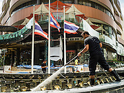 15 OCTOBER 2016 - BANGKOK, THAILAND: A worker, wearing black for mourning, cleans a fountain in front of Thai flags at half staff at Gateway Center, a shopping mall in Bangkok. Thai King Bhumibol Adulyadej died Oct. 13, 2016. He was 88. His death comes after a period of failing health. With the king's death, the world's longest-reigning monarch is Queen Elizabeth II, who ascended to the British throne in 1952. Bhumibol Adulyadej, was born in Cambridge, MA, on 5 December 1927. He was the ninth monarch of Thailand from the Chakri Dynasty and is known as Rama IX. He became King on June 9, 1946 and served as King of Thailand for 70 years, 126 days. He was, at the time of his death, the world's longest-serving head of state and the longest-reigning monarch in Thai history.      PHOTO BY JACK KURTZ