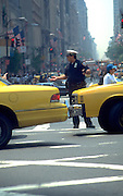 Traffic cop age 30 standing in street directing traffic.  New York  New York USA