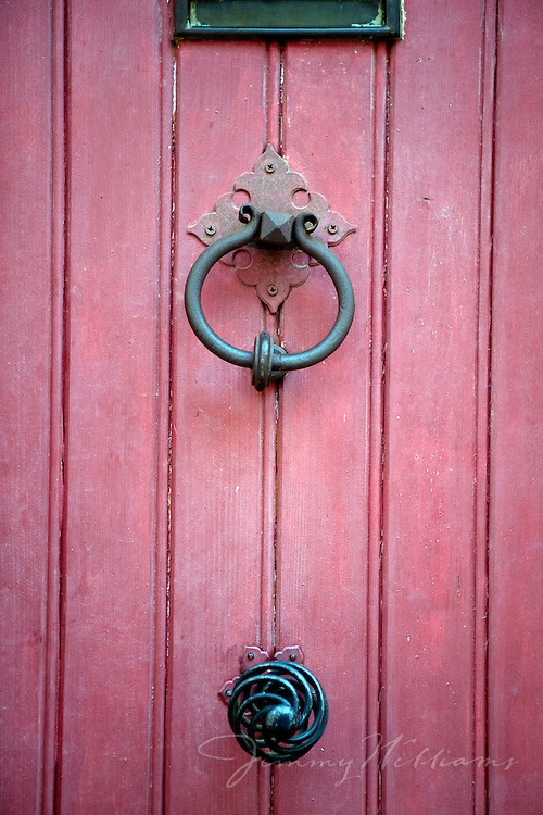An old metal door knocker is mounted to a red wooden door on a home in Roussillon, France