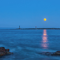 Massachusetts seascape photography of a Full Moon Rise over Thacher Island Twin Lights at dusk. The South Tower and North Tower lighthouses are located on Cape Ann, Massachusetts.<br />