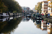 House boats on the Regents Canal in Hackney during the second coronavirus national lockdownon on 7th of November 2020, East London, United Kingdom. The canal is home to many living in boats and the canal has become both a home to many and a place to spend time on a sunny day. The lockdown restrictions mean that people are only allowed to meet outside, in pairs and only if keeping social distance.