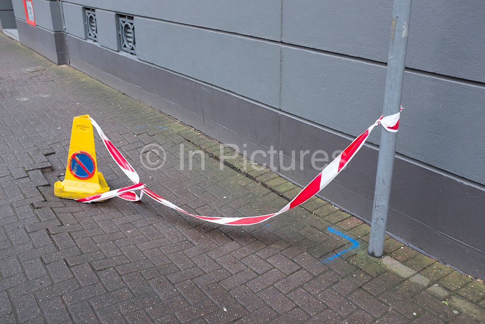 Police cone teathered to a lamppost with red and white warning tape. This is warning the public of an uneven area of pavement. London, UK.