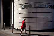 Scene in the City of London in the afternoon winter light as a woman walks past building at One London Wall.