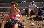 A baby enjoys the sandy beach with his parents at Minehead, on 12th August 1993, in Minehead, England.