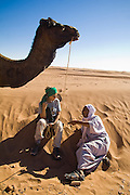 Camel guide Elhussein Sbiti speaks with his female American client under a camel on a three-day trek to the remote sand dunes of Erg Zehar, near M'hamid in the Moroccan Sahara. Sbiti, like many berber nomads in the region, has found opportunity in the new tourism trade burgeoning since the settling of tensions between Morocco and neighboring Algeria..