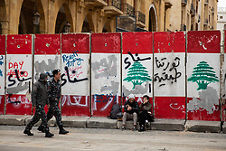 © Licensed to London News Pictures. 27/01/2020. Beirut, Lebanon. Lebanese police walk past two people sitting on a graffitied security wall around the government buildings in Downtown Beirut, as the government votes on the 2020 budget. Anti government demonstrators have been campaigning against government corruption and economic crisis for 103 days in Lebanon. Photo credit : Tom Nicholson/LNP