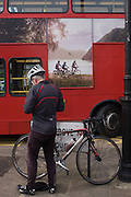 Cyclist and cycling holiday ad on side of red London bus.