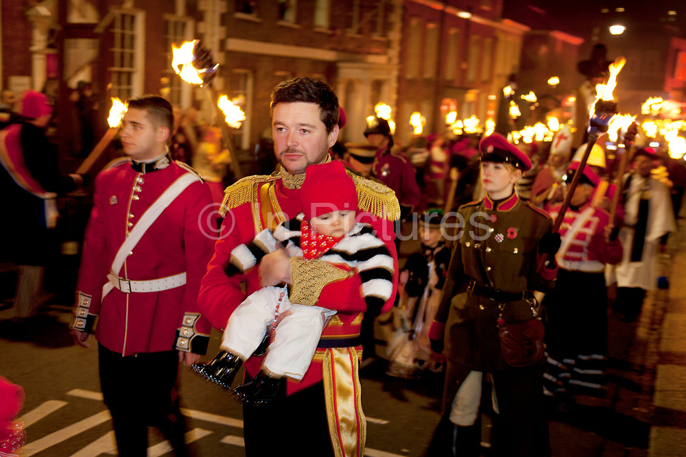 Lewes, UK. Monday 5th November 2012. Cliffe bonfire society member carries his child. Bonfire Night celebration in the town of Lewes, East Sussex, UK which form the largest and most famous Guy Fawkes Night festivities. Held on 5 November, the event not only marks the date of the uncovering of the Gunpowder Treason and Plot in 1605, but also commemorates the memory of the 17 Protestant martyrs from the town burnt at the stake for their faith during the Marian Persecutions of 1555–57. There are six bonfire societies putting on parades involving some 3,000 people.