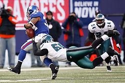11 Jan 2009: Philadelphia Eagles defensive end Trent Cole #58 gets his arms around New York Giants running back Derrick Ward #34 during the game against the New York Giants on January 11th, 2009.  The  Eagles won 23-11 at Giants Stadium in East Rutherford, New Jersey. (Photo by Brian Garfinkel)