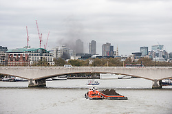 © Licensed to London News Pictures. 11/11/2015. London, UK. Huge plumes of black smoke can be see over the capital's skyline.  A fire burning in a building on Fleet Street, to the left of the Goldman Sachs building.  A sign labelled Mary Queen of Scots house stands above the doorway.  Several fire engines, their crew and police are in attendance.  At present the cause is unknown. Photo credit : Stephen Chung/LNP