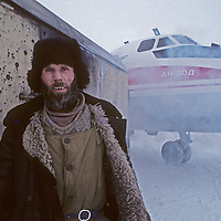 Despite winter cold, a Russian airport worker tends a plane on Severnaya Zemlya, an archipeligo far north of Siberia.