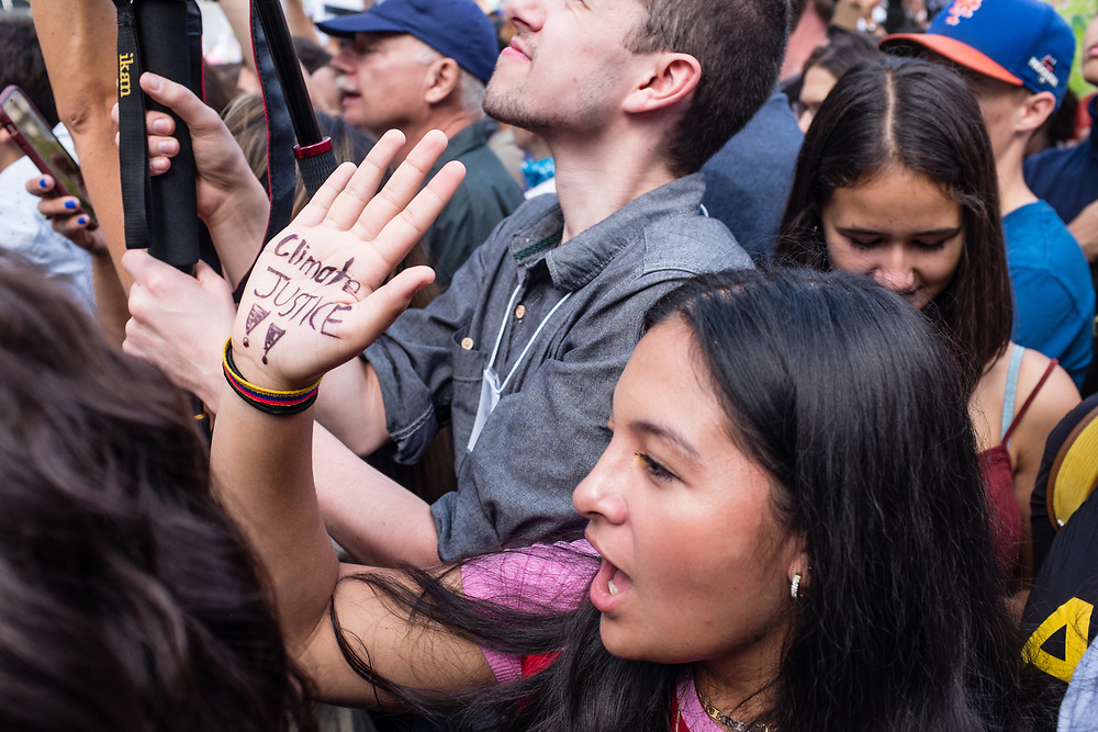 "20 September 2019 - New York, NY.  Thousands of students as well as adults gathered in New York for the Global Climate Strike, meeting in Foley Square near the Federal Government buildings and New York's City Hall, and marching downtown to Battery Park, where Swedish climate activist and spokesperson Greta Thunberg addressed the crowd. A young woman holds her hand up, on the palm of which is written ""Climate Justice!!"""