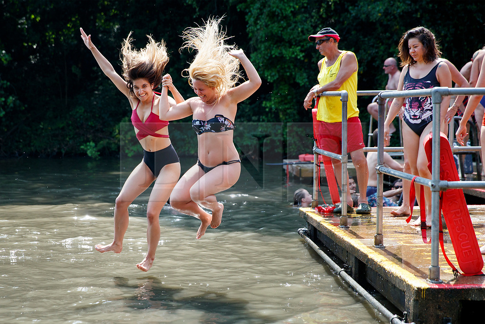 © Licensed to London News Pictures. 21/06/2017. London, UK. Melanie Leppard and Sammi Lord jump into Hampstead Heath Mixed Bathing Pond in north London as temperatures hit 34C and makes it the hottest UK June day since 1976 on Wednesday, 21 June 2017. Photo credit: Tolga Akmen/LNP