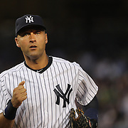 Derek Jeter, New York Yankees, heads back to the dugout after fielding at shortstop during the New York Yankees Vs Cincinnati Reds baseball game at Yankee Stadium, The Bronx, New York. 18th July 2014. Photo Tim Clayton
