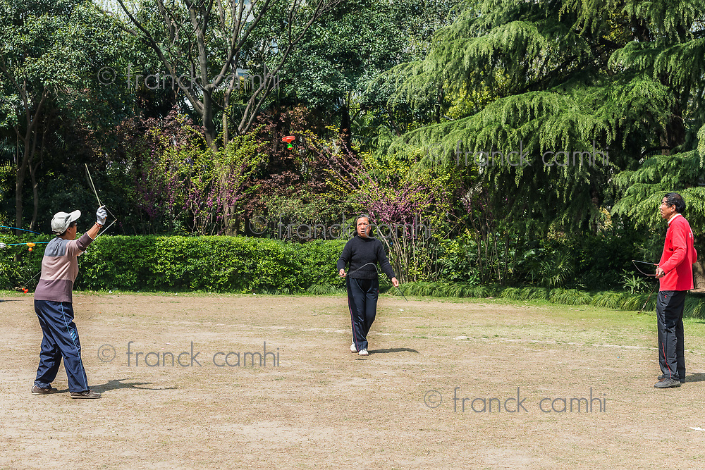 Shanghai, China - April 7, 2013: old people playing diabolo in fuxing park at the city of Shanghai in China on april 7th, 2013