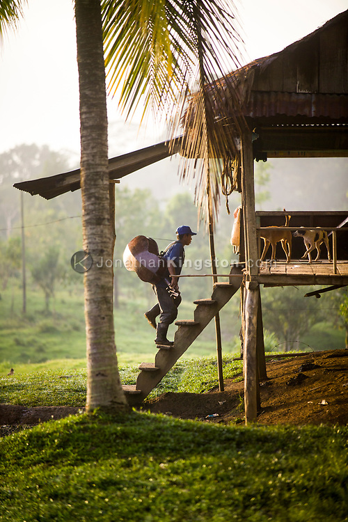 A Miskito man carries a string bass into a cabin in Krin Krin, Nicaragua.