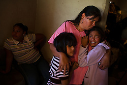 Two young girls are comforted by their aunt during the wake of their mother in the state of Chihuahua, near Ciudad Juarez.  The mother was a factory work and was killed during a shooting on the bus that was taking her home.