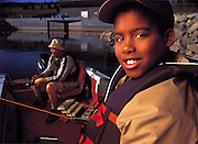 A young african-american boy smiles while fishing with his family on a lake in Colorado