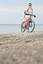 Mature woman with bicycle at lakeshore, Bavaria, Germany