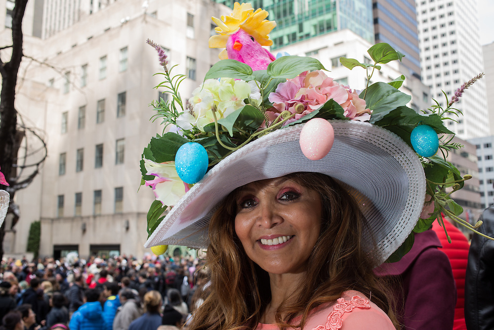 New York, NY, USA-27 March 2016. A woman wears a hat decorated with flowers and colored eggs, and topped by a pink chicken, in the annual Easter Bonnet Parade and Festival.