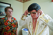 "Aug. 2 - PHOENIX, AZ: JANE TRAPANI watches her husband, DONALD TRAPANI, finish dressing as Elvis Presly before he performed as the ""King"" at the Stratford, an Alzheimer's care facility in Phoenix. Trapani, 68, was diagnosed with lung cancer in August 2009 and entered the care of Hospice of the Valley, the largest hospice organization in Phoenix, shortly after that. His doctor said he would be dead by the end of February 2010. Trapani is in still in the care of Hospice of the Valley, but his condition has improved. He now entertains other hospice patients singing the songs of Elvis Presley. He tries to hold one concert each week, his health permitting, at different hospice units in the Phoenix area.     Photo by Jack Kurtz"