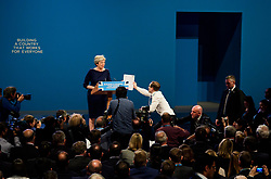 © Licensed to London News Pictures. 04/10/2017. Manchester, UK. Security watch over as British prime minister THERESA MAY is handed a fake P45 form by a protestor, watched over by BORSI JOHNSON (pictured right) during leaders speech on the final day of the Conservative Party Conference. The four day event is expected to focus heavily on Brexit, with the British prime minister hoping to dampen rumours of a leadership challenge. Photo credit: Ben Cawthra/LNP