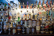 Whiskey and spirit bottles lined up along bar, Georgetown, Washington DC, USA