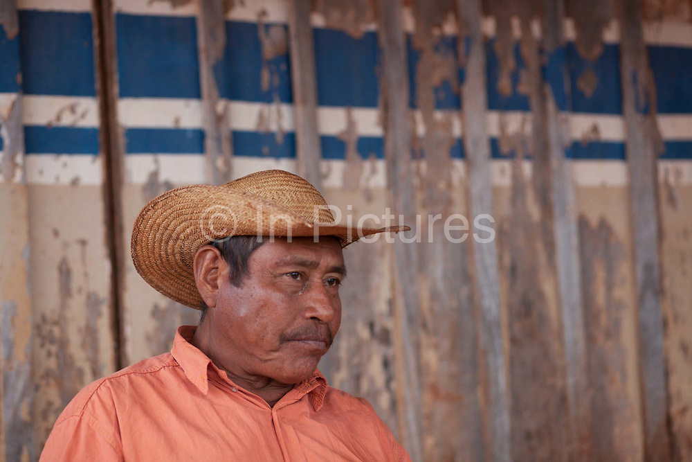 Guarani man sitting in a wooden house wearing a straw hat. The Guarani are one of the most populous indigenous populations in Brazil, but with the least amount of land. They mostly live in the State of Mato Grosso do Sul and Mato Grosso. Their tradtional way of life and ancestral land is increasingly at risk from large scale agribusiness and agriculture. There have been recorded cases and allegations of violence between owners of large farms and the Guarani communities in this region.