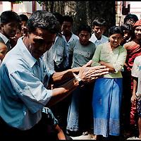 Burmese man performing tricks in front of a small crowd at Mandalay