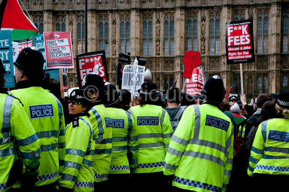 November 21st. Westminster. Demonstration organised by National Union of Students (NUS) against education cuts. A line of police protect the Houses of Parliament from students with placards protesting government education policy.