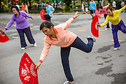 06 OCTOBER 2012 - BANGKOK, THAILAND:  Women do Tai Chi exercises with fans in Lumphini Park in Bangkok. The Thai government promotes exercise classes as a way staying healthy. Lumphini Park is 142 acre (57.6-hectare) park in Bangkok, Thailand. This park offers rare open public space, trees and playgrounds in the congested Thai capital. It contains an artificial lake where visitors can rent boats. Exercise classes and exercise clubs meet in the park for early morning workouts and paths around the park totalling approximately 1.55 miles (2.5km) in length are a popular area for joggers. Cycling is only permitted during the day between the times of 5am to 3pm. Smoking is banned throughout smoking ban the park. The park was created in the 1920's and named after Lumbini, the birthplace of the Buddha in Nepal.   PHOTO BY JACK KURTZ
