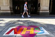 A man and his wife walks past a message of love for the National Health Service (NHS), painted on the ground outside Selfridges department store on a near-deserted Oxford Street in London on Thursday, May 28, 2020. The government in Britain eased restrictions across England as a slow loosening of the coronavirus lockdown gets underway, with people now encouraged to return to work if unable to do so from home and unlimited outdoor exercise now allowed. As the row over Prime Minister Boris Johnson's top aide Dominic Cummings' Durham trip, continues, the prime minister's populist appeal has been hammered by the news that, as the coronavirus outbreak raged, chief adviser Cummings drove 250 miles (400 kilometres) to his parents' house while he was falling ill with suspected COVID-19 allegedly flouting lockdown rules that the government had imposed on the rest of the country. (Photo/ Vudi Xhymshiti)