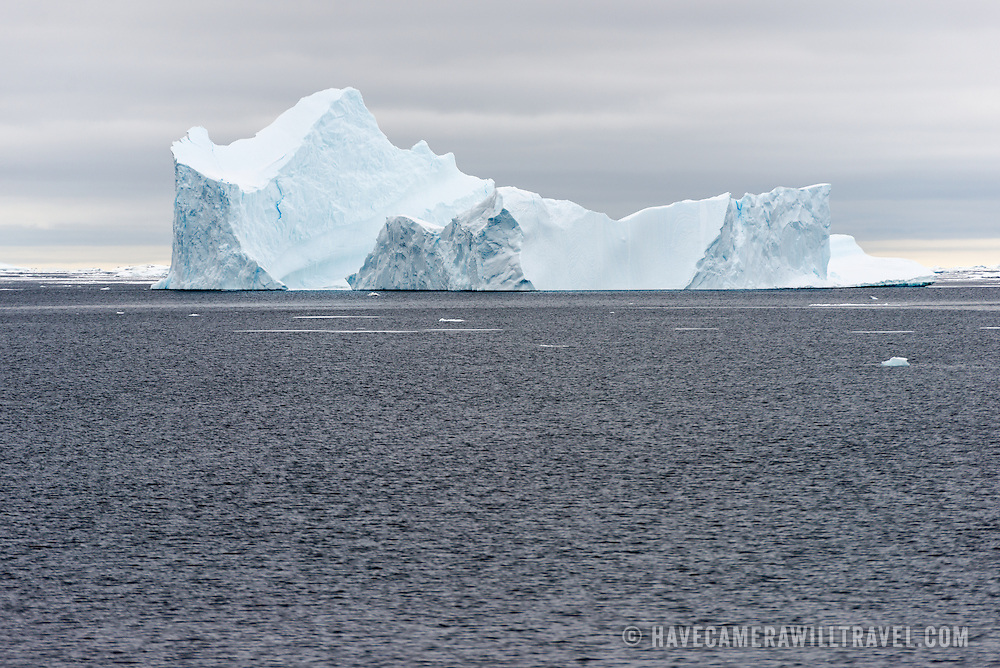 An iceberg with steep jacked sides floats on the gray waters in the Argentine Islands on the western side of the Antarctic Peninsula.