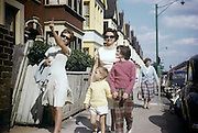 A family walk along a town's side street during summer time in the early 1960s. A small boy is accompanied by his older sister who points at something in the distance, his mother wearing pearls behind and a family friend who holds his hand as the walk towards the town's new shopping precinct. The picture was recorded on a film camera by the boy's father, an amateur photographer in 1962. The picture shows us a memory of nostalgia in an era from the last century.