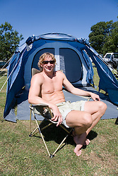 Man sitting outside tent; camping,