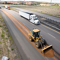 090613     Brian Leddy<br /> A New Mexico Department of Transportation crew spreads sand on an oil slick on the eastbound onramp of Interstate 40 at exit 20 Friday afternoon. The vehicle that caused the spill was not identified.